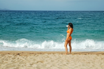 Attractive woman on tropical beach taking photo with camera