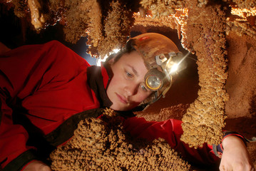 Caver girl with beautiful stalactites in a cave
