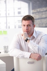 Mature man sitting in office thinking