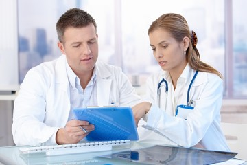 Young doctors discussing diagnosis in office