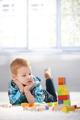 Adorable gingerish little boy with building cubes