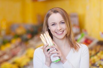 frau kauft spargel in der gemüseabteilung