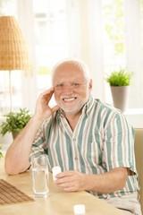Smiling senior holding medication