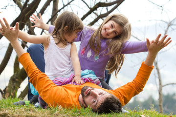 Father playing with his daughters in the park