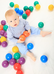 baby with balls on the bed