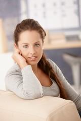 Portrait of pretty girl sitting on sofa smiling
