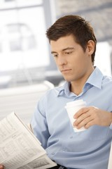 Young businessman on break reading papers