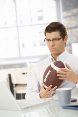 Determined businessman in office with football