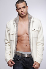 Stylish young fashion male model on gray background.