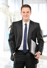 Smiling businessman holding a laptop and posing in his office