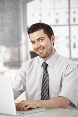 Happy office worker sitting at desk using laptop