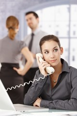 Young secretary on the phone in office