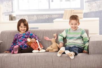 Happy kids sitting on sofa