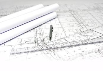 ołówek i rulony na białym planie budowy architektonicznym