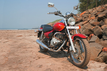 Cruiser motorcycle at sand rocky beach india