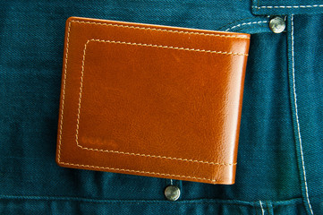 Blue jeans pocket with brown wallet