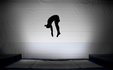 Wall Mural - silhouette of jumping man on trampoline doing somersault