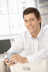 Coffee break in office, smiling businessman