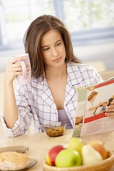 Woman reading magazine at breakfast