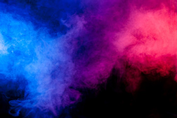 Red and blue smoke on black background