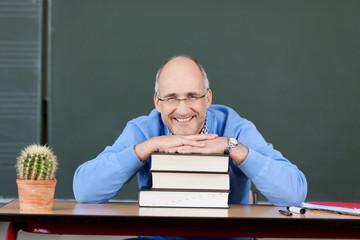 lächelnder professor stützt sich auf bücher