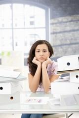 Troubled secretary sitting among folders