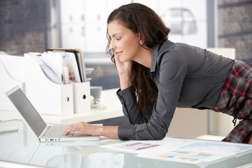 Young businesswoman using laptop in office