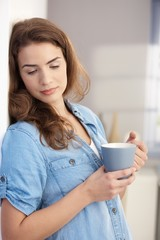 Daydreaming woman drinking tea at home