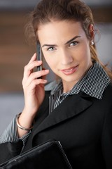 Young businesswoman smiling happily with mobile