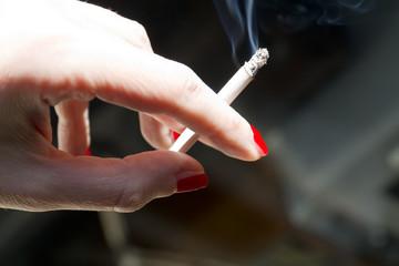 Mano di donna che tiene una sigaretta fumante