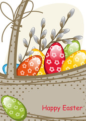Willow branches in the basket, colorful Easter eggs