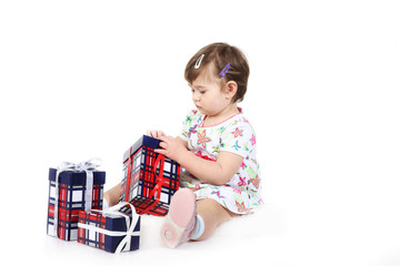 little girl sits with three gift boxes.