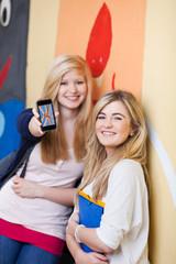 zwei schülerinnen zeigen foto auf dem handy