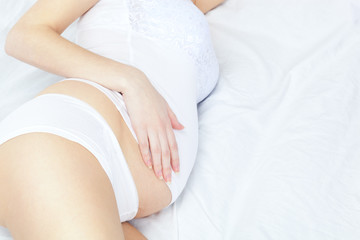 pregnant woman on white bed