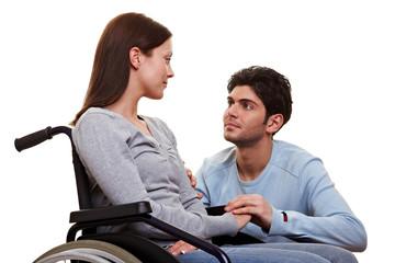 Mann pflegt Frau im Rollstuhl