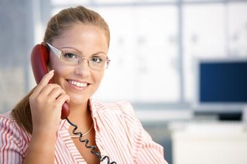 Pretty receptionist working talking on phone