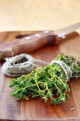 bunch of fresh thyme and a knife on a wooden board