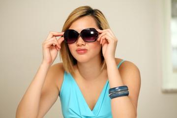 Cute elegant girl trying on sunglasses