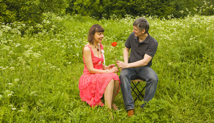 Man presents woman red rose