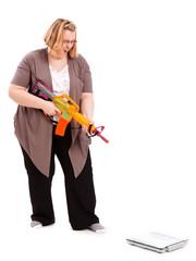 junge dicke Frau, die eine Waage bekämpfen will
