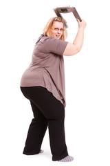 dicke Frau, die eine Waage zerstören will