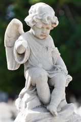 Weathered child angel statue with a  vegetation background