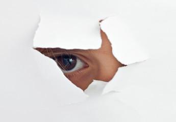 A child's eye peeking through a hole in a white paper sheet