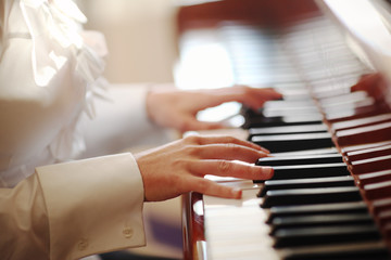 Female hands playing piano. Closeup, shallow DOF.