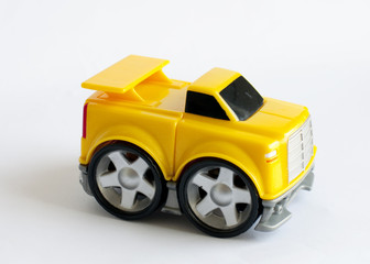 A childs chunky yellow toy car isolated on white