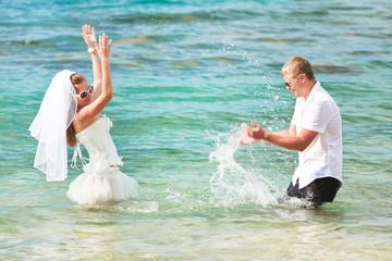Groom and bride splashing a water