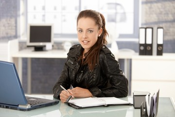 Young woman working in office smiling