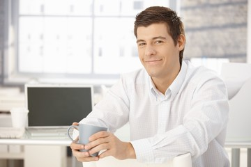 Portrait of content businessman with cup