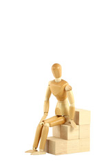 Wooden manikin sitting on blocks
