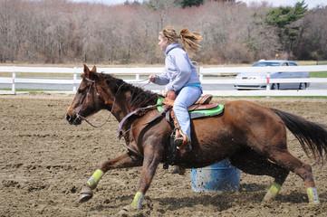 Young blonde woman barrel racing